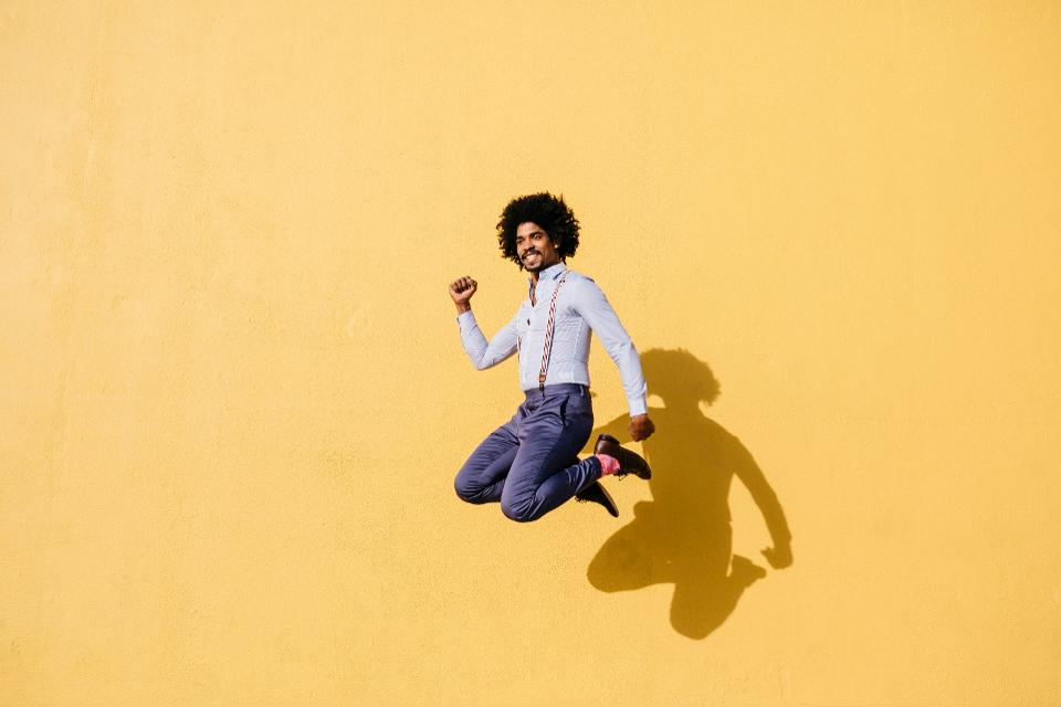 Smiling man jumping in the air in front of yellow wall