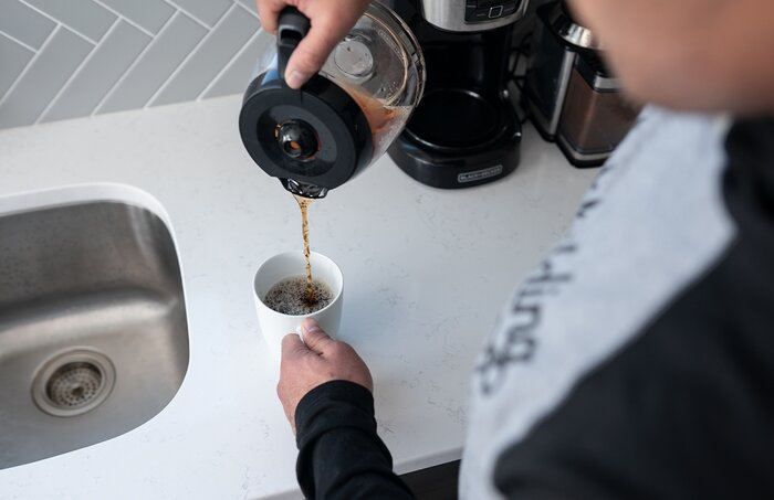 Pouring a cup of coffee.