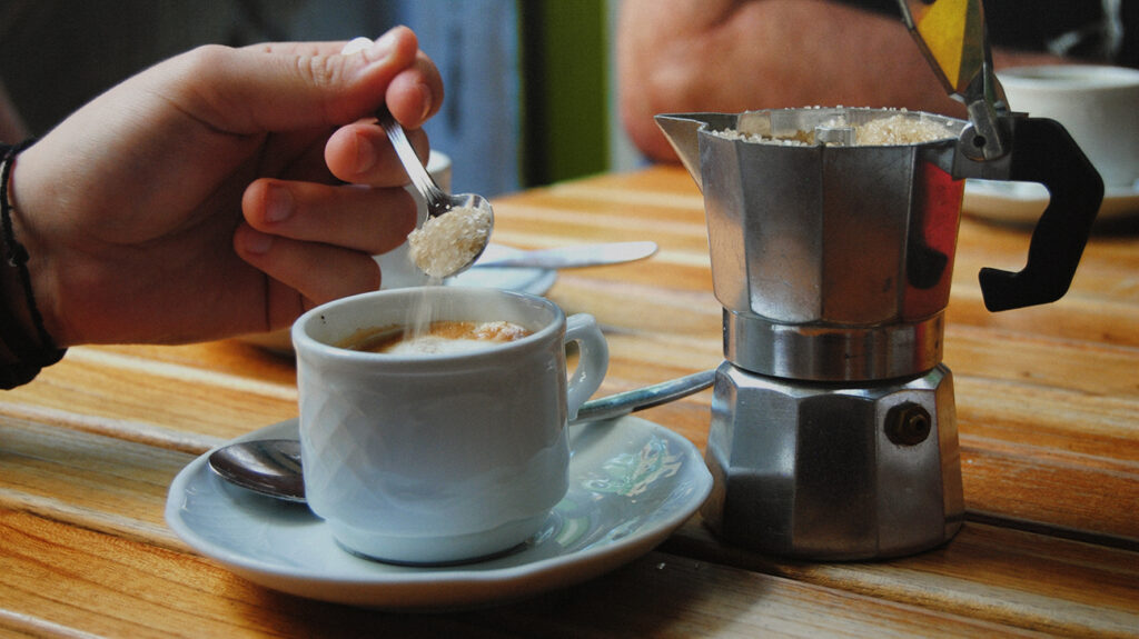 close up of hand picking up sugar-filled teaspoon for coffee