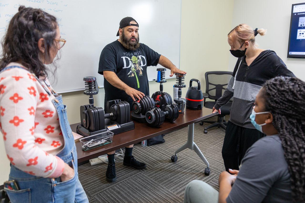 A Nautilus employee explains several of the company's personal fitness products to co-workers