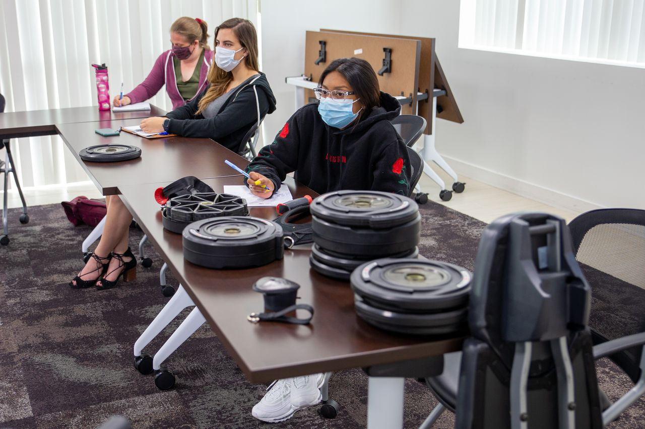 Nautilus employees sit at a table covered with weight plates during a product training session
